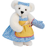 """15"""" Cooking Bear - Three quarter view of standing jointed bear dressed in a blue floral sundress and oven mitt, yellow apron with pink trim and holding a wooden spoon. Apron is personalized with """"Julietta"""" in hot pink - Vanilla white fur image number 2"""