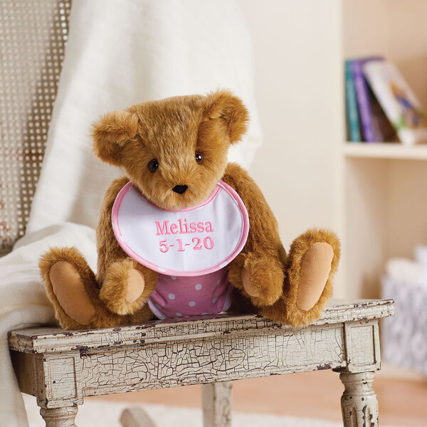 """15"""" Baby Girl Bear - Jointed honey bear dressed in pink with white dots fabric diaper and bib sitting on a table with a bookcase behind it.  image number 11"""