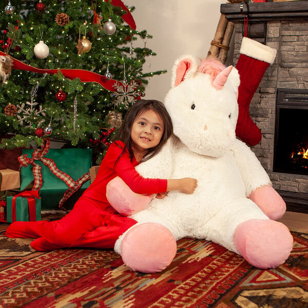 "4' Unicorn - Front view of ivory 48"" unicorn with pink hooves, main, horn and tail in a Christmas scene with a girl in red pajamas image number 3"