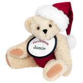 "15"" Baby's First Christmas Bear - Seated jointed bear dressed in red velvet diaper with santa hat and white and green bib that says ' First Christmas' in red lettering. Bib is personalized with ""Jamie"" in dark green lettering - Buttercream brown fur image number 1"