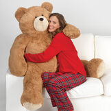 4' Big Hunka Love Bear - Seated golden brown bear with a female model in red pajamas on a sofa image number 0