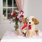 """15"""" Classic Puppy Dog - Seated on a table with rose petals and a bouquet of flowers, jointed tan puppy dog with honey brown spots, ears and tail is dressed in a red satin bow with pink heart in center - Buttercream brown fur image number 9"""