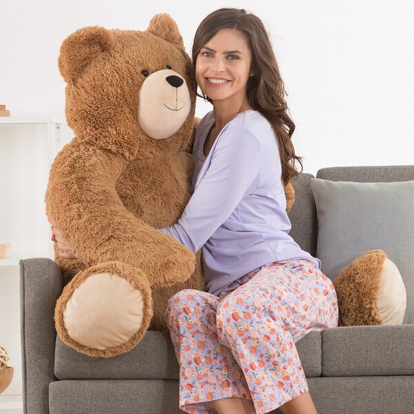 4' Big Hunka Love Bear - Seated golden brown bear with a female model in lavender pajamas on a sofa image number 6