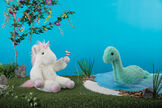 "18"" Fluffy Fantasies Dinosaur - Close up of Green aquatic plush dinosaur with iridescent satin details sitting in a lake with 18"" Unicorn on the shore image number 1"
