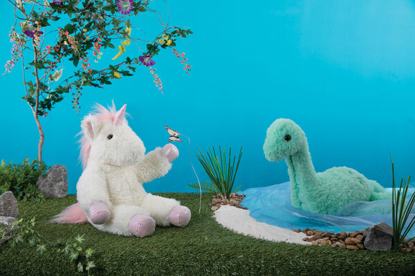 """18"""" Fluffy Fantasies Dinosaur - Close up of Green aquatic plush dinosaur with iridescent satin details sitting in a lake with 18"""" Unicorn on the shore image number 1"""