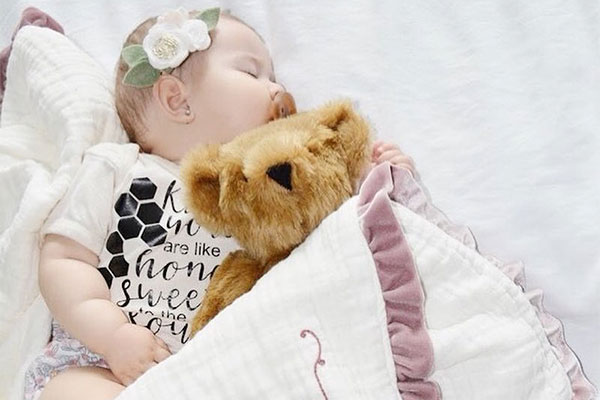 An image of a baby laying with a 15-inch Baby Girl Bear