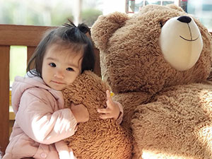 An image of a child cuddling a Vermont Teddy Bear