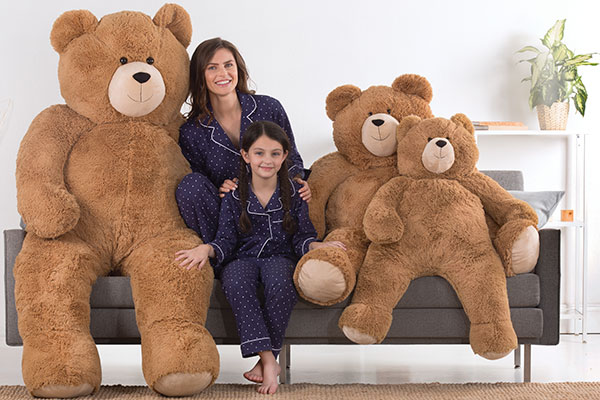 An image of a woman and a child sitting with a 4-foot Big Hunka Love Bears