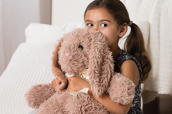 An image of a young child cuddling with the World's Softest Bunny