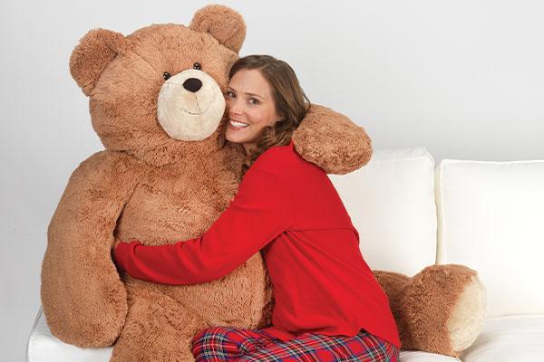 An image a model cuddling a 4-foot Big Hunka Love Bear