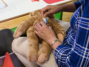 An image of a worker sewing a Vermont Teddy Bear