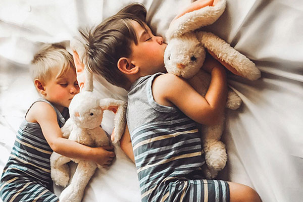 An image of 2 sleeping children cuddling with The World's Softest Bunny bears