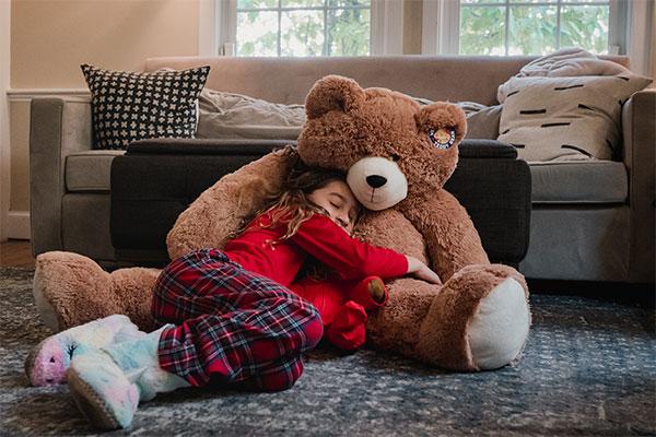 An image a child cuddling a 4-foot Big Hunka Love Bear