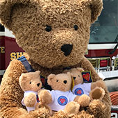 The official Vermont Teddy Bear mascot posing with 3 Make a Friend For Life Teddy Bears