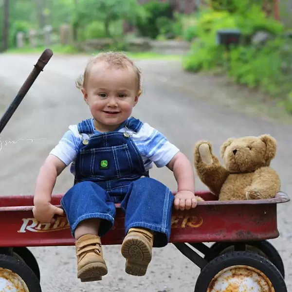 A photo of a child with a Vermont Teddy Bear classic bear