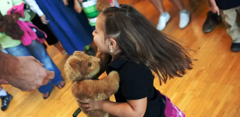 An image of a girl dancing with a teddy bear