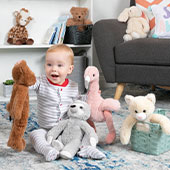 A young infant playing on the floor with bears from the Buddy Collction