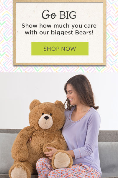 An image of of a model playing with the 3-foot Hunka Love teddy bear