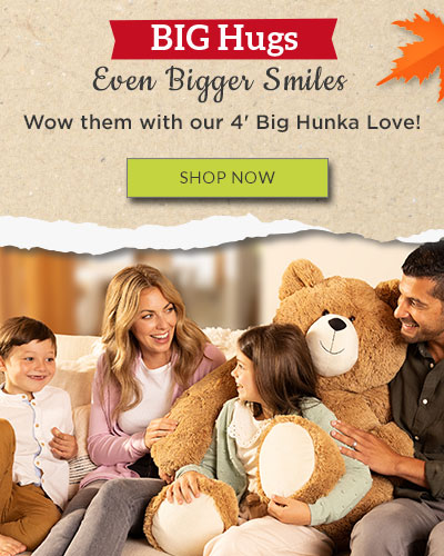 A photo of a Mom, Son, Daughter and Father sitting on a couch with the 4-foot Big Hunka Love Bear