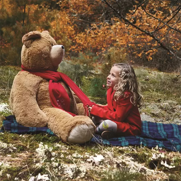 A photo of a child with a Vermont Teddy Bear 4-foot Big Hunka Love bear