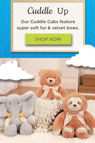 An image of the 13-inch Cuddle Cub Collection sitting in a basket of blankets