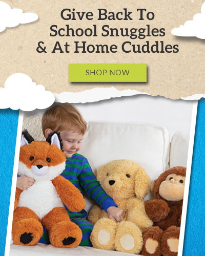 An image of the a small child sitting on a couch next to an 18-inch Oh So Soft Fox Dog and Monkey