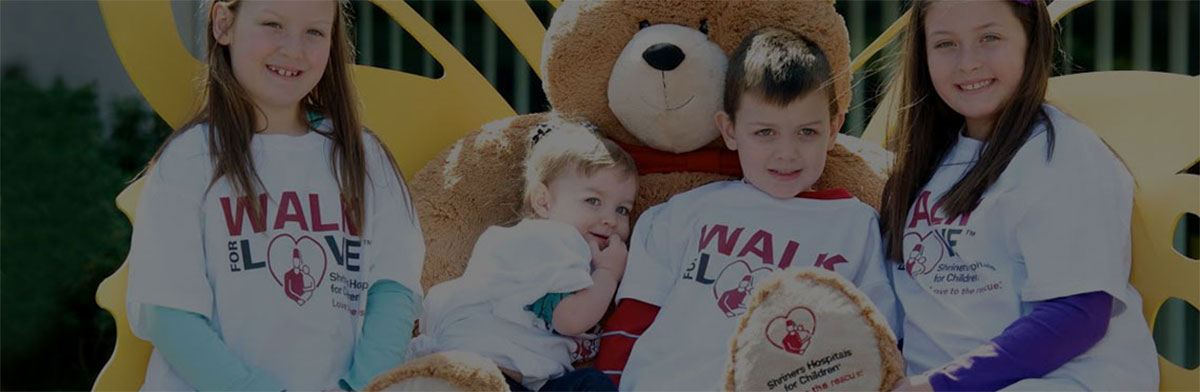 An image of children sitting with the 4-foot Love to the Rescue Bear