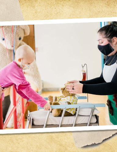 A young girl playing with a teddy bear and Cassie, our teddy bear designer, while taking a tour of our factory